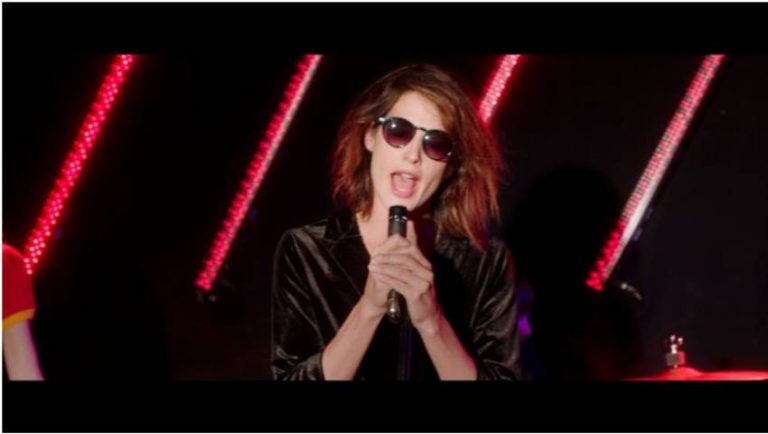 A still from Songbird. Cobie Smulders wearing dark glasses and a leather jacket is singing on a stage